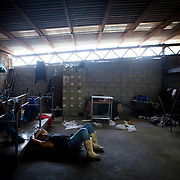 An employee takes a rest on the floor after slicing fish at a fish wholesaler on Thursday, May 16, 2013 in Tijuana, Mexico.