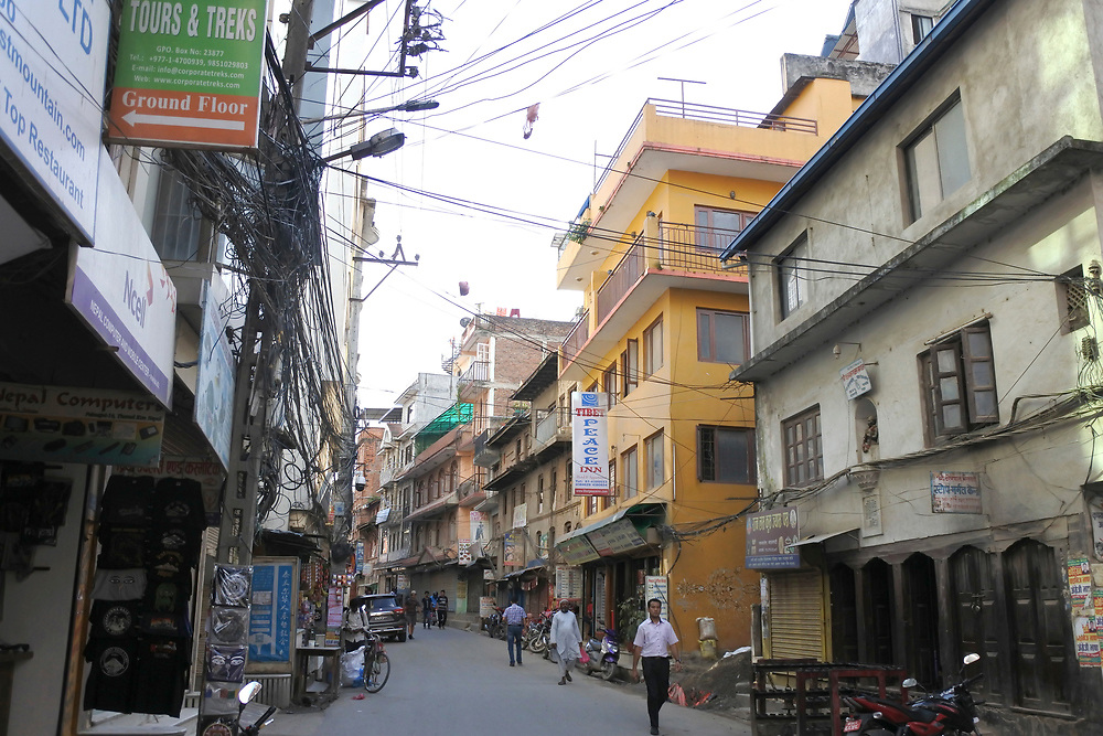Side street in Kathmandu with flags and electrical lines