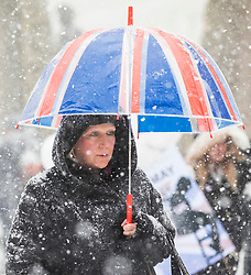 © Licensed to London News Pictures. 28/02/2018. London, UK. A woman shelters beneath a Union Jack umbrella on Whitehall as heavy snow falls in central London. Severe weather is set to continue as the 'Beast from the East' brings freezing Siberian air to the UK. Photo credit: Rob Pinney/LNP