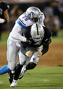Oakland Raiders rookie quarterback Derek Carr (4) gets driven to the ground and out of the game with a concussion on a hard tackle by Detroit Lions defensive end Larry Webster (79) in the fourth quarter during the 2014 NFL preseason football game against the Detroit Lions on Friday, Aug. 15, 2014 in Oakland, Calif. The Raiders won the game 27-26. ©Paul Anthony Spinelli