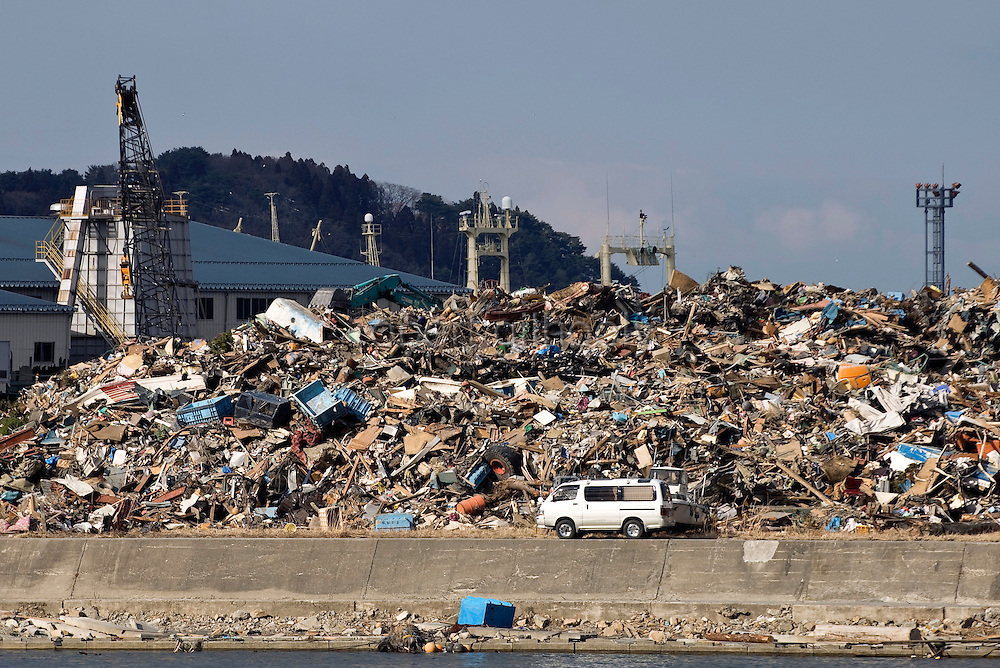 Cranes and trucks dump debris from the March 11 tsunamis onto a growing mountain of debris in Miyako, Iwate Prefecture, Japan on 03 April, 2011. The amount of waste left by the disasters has been estimated to be as much as 27 million tons. Photographer: Robert Gilhooly