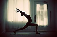 Moody warrior asana silhouette in a small intimate yoga studio.<br />