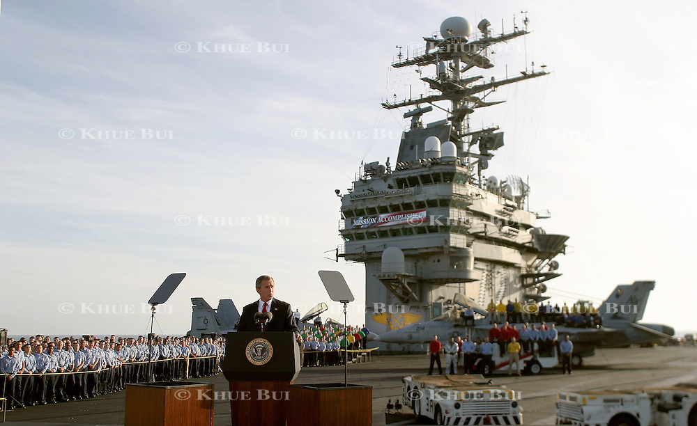 President Bush addresses the nation on the flight deck of the aircraft carrier USS Abraham Lincoln Thursday, May 1, 2003, in the Pacific Ocean.  Bush traveled to the aircraft carrier USS Abraham Lincoln to meet with returning sailors and to announce and end to 'major combat operations' in Iraq.  The banner in the background says 'Mission Accomplished'..Photo by Khue Bui