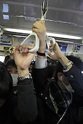 commuter train at rush hour full with business people Tokyo Japan
