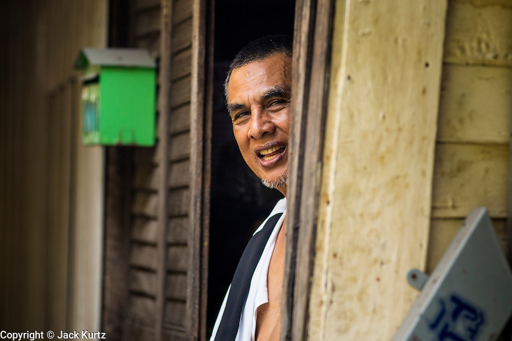 """11 JANUARY 2013 - BANGKOK, THAILAND:    A Muslim man stands in the doorway of his home in the Ban Krua neighborhood in Bangkok. The Ban Krua neighborhood of Bangkok is the oldest Muslim community in Bangkok. Ban Krua was originally settled by Cham Muslims from Cambodia and Vietnam who fought on the side of the Thai King Rama I. They were given a royal grant of land east of what was then the Thai capitol at the end of the 18th century in return for their military service. The Cham Muslims were originally weavers and what is known as """"Thai Silk"""" was developed by the people in Ban Krua. Several families in the neighborhood still weave in their homes.                PHOTO BY JACK KURTZ"""