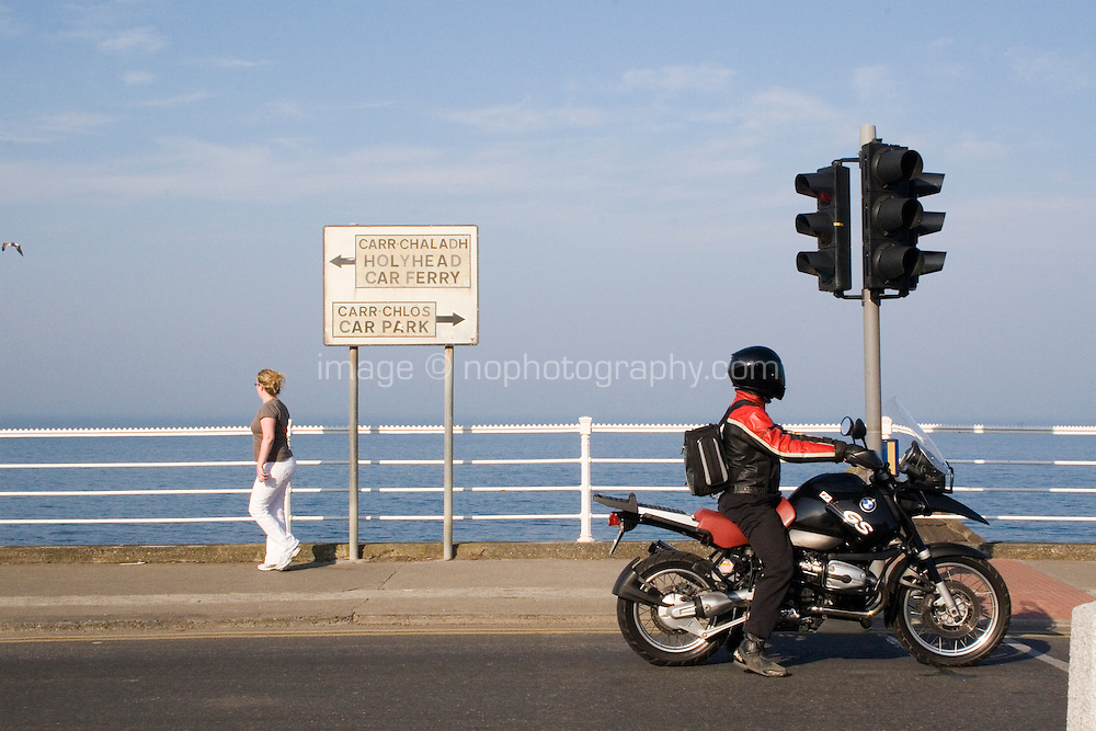 Dun Laoghaire Seafront in Dublin Ireland. Woman walking along seafront and motorbike waiting at traffic lights. Sign for the car ferry to Hollyhead in Wales.