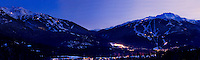 The dual mountains of Whistler and Blackcomb glow at sunset on a winter night in the ski resort of Whistler, BC Canada