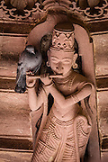 Inside a hindu temple in the castle of Jodhpur, a pigeon rests in a statue of a music player, using the flute as a perch.
