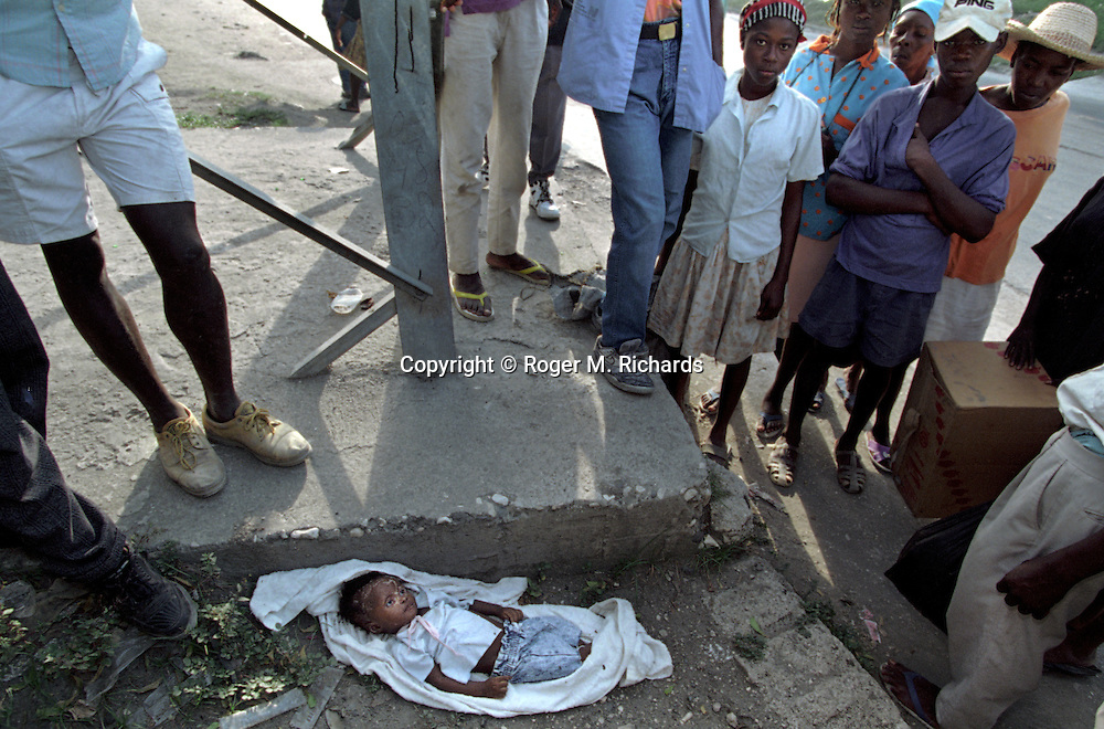A crowd gathers around the body of a small child that was evidently killed (a pink ribbon was knotted tightly around the child's throat) and dumped by the roadside  in Port-au-Prince, Haiti, May 1995. (Photo by Roger M. Richards)
