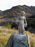 An old marble statue of a girl, maybe bringing lunch to the miners, sits above Skippers Canyon and the Shotover River, speaking, perhaps of the historic gold mining life this area once hosted, near Queenstown, Otago, New Zealand.