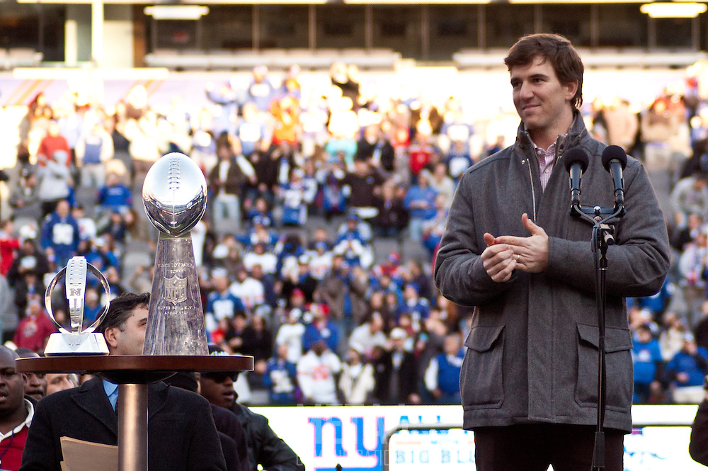 Giants' Head Coach Tom Coughlin applauds with Justin Tuck and Eli Manning as Master of Ceremonies Bob Papa conducts the championship celebration.