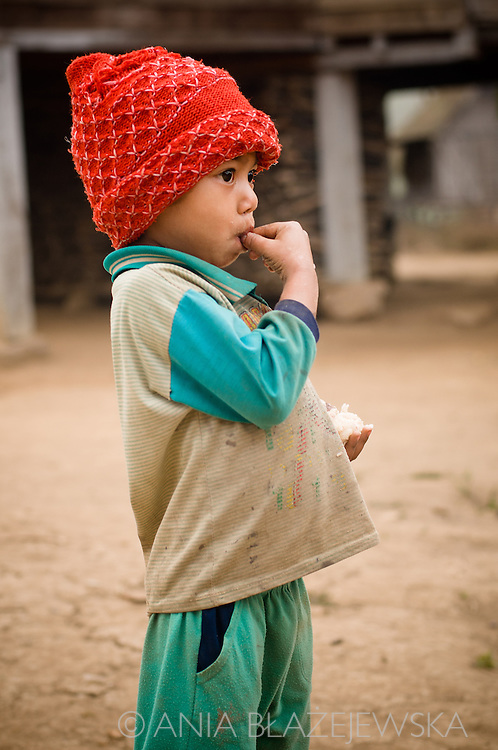 Laos, Ban Nam Pick. A little Khamu boy wearing a red hat.