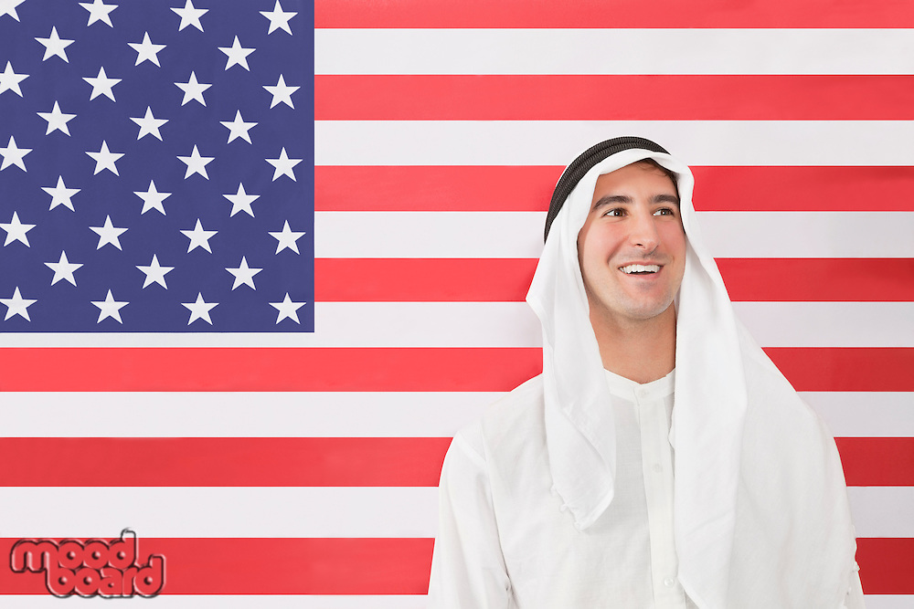 An Arab man in traditional clothes looking away against American flag