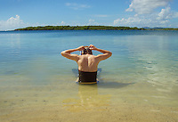 woman adjusts her mask before going snorkeling off Blue Beach in Vieques, Puerto Rico