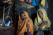 Rohingya refugee crisis. Shafiqa Begum, (21), with her sister, Roshida Begum 24. Survivors of the massacre at Tula Toli (Min Gyi village) in Myanmar inside their make-shift shelter at the Balukhali refugee camp at Cox's Bazar District, Bangladesh - Photograph by David Dare Parker