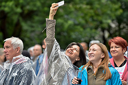 """© Licensed to London News Pictures. 22/07/2017. London, UK. """"Nashville Meets London"""", a country music festival, takes place in Canary Wharf.  Heavy rain fails to dampen the enjoyment of dedicated country music fans, many wearing protective ponchos, watching artists from the UK as well as the USA for the two day weekend festival. Photo credit : Stephen Chung/LNP"""