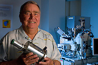 Dr. Klaus Kiel holding the original original solid state energy dispersive spectrometer while standing in front of the new generation equipment.  University of Hawaii