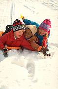 Friends age 7 through 10 falling off snow sled. St Paul Minnesota USA