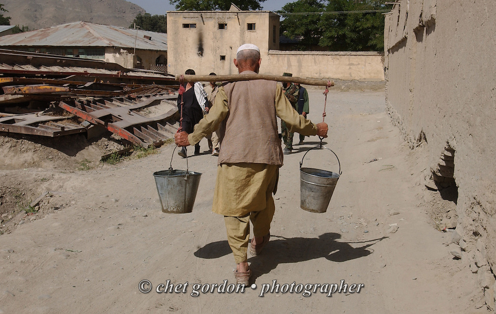 A man carries two buckets of water from a hand water pumping station on a back street in Kabul, Afghanistan on Sunday, May 26, 2002.