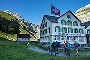 Altmann peak (2435m) rises dramatically above Meglisalp, in morning light. Berggasthaus Meglisalp can only be reached on foot in the spectacular heart of the Alpstein mountain chain in the Appenzell Alps, Switzerland, Europe. This authentic mountain hostelry, owned by the same family for five generations, dates from 1897. Meglisalp is a working dairy farm, restaurant and guest house surrounded by majestic peaks above green pastures. For licensing options, please inquire.