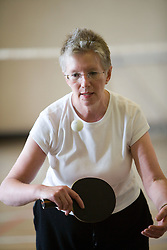 Older woman playing table tennis in a community centre sports hall,