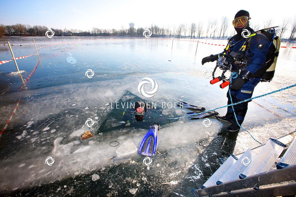 ZALTBOMMEL - Diversen duikers gingen door een zelfgemaakt wak in de Tijningense Plas, ook wel put van zanen genoemd, ijsduiken. FOTO LEVIN DEN BOER - PERSFOTO.NU