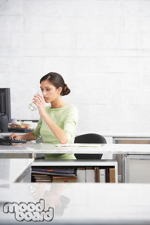 Young woman in office drinking water from glass