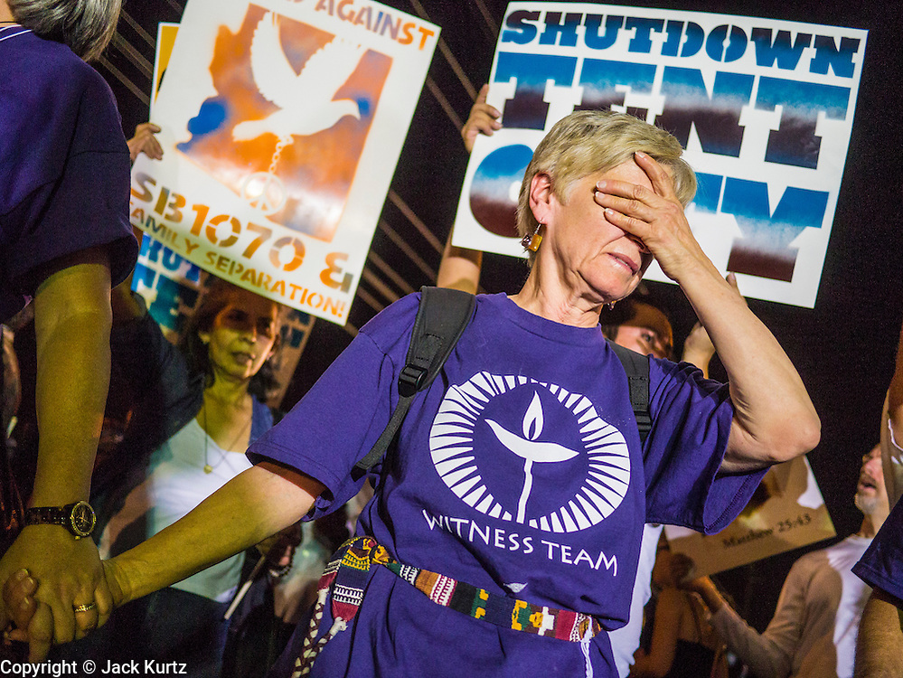 """23 JUNE 2012 - PHOENIX, AZ:   A member of the Unitarian """"witness team"""" tries to control the crowd during a protest against the Maricopa County Jail system in Phoenix Saturday. About 2,000 members of the Unitarian Universalist Church, in Phoenix for their national convention, picketed the entrances to the Maricopa County Jail and """"Tent City"""" Saturday night. They were opposed to the treatment of prisoners in the jail, many of whom are not convicted and are awaiting trial, and Maricopa County Sheriff Joe Arpaio's stand on illegal immigration. The protesters carried candles and sang hymns.    PHOTO BY JACK KURTZ"""