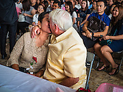 """14 FEBRUARY 2017 - BANGKOK, THAILAND: A couple kisses after getting married in the Bang Rak district in Bangkok. Bang Rak is a popular neighborhood for weddings in Bangkok because it translates as """"Village of Love."""" (Bang translates as village, Rak translates as love.) Hundreds of couples get married in the district on Valentine's Day, which, despite its Catholic origins, is widely celebrated in Thailand.      PHOTO BY JACK KURTZ"""