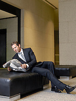 Businessman reading newspaper in lobby