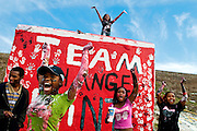 From left, Delaney Harris, 20; Aaliyah Strickland, 16; Da'Licia Smyers (top), 16;  Chantell Harrison, 20; and Breanna Willis, 19 cheer as passing cars honk their horns. The group pictured here, and several others, organized on Facebook to paint the rock on Twelfth Street and Hammerberg Road in a effort to bring about positive change in the city of Flint.