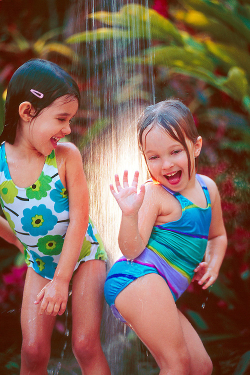 Two young girls play in outdoor shower.