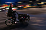 A long-exposure blurry photo of a cyclist in Nørrebro Copenhagen.