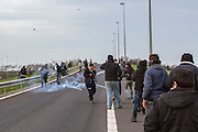 FRANCE, Calais: 17 December 2015 Refugees run from tear gas grenades whilst clashing with riot police outside of the Euro Tunnel entrance in Calais this afternoon. Hundreds of refugees walked hours through Calais today to reach the Euro Tunnel from 'The Jungle' camp to try and get to England. Rick Findler  / Story