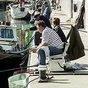 NLD/Huizen/ - leden van een visvereniging op en rij op de kade, heerlijk zitten din de zon