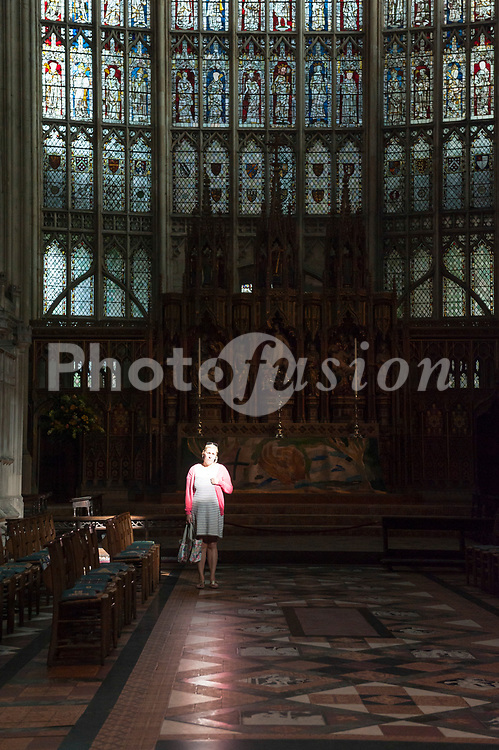 A woman stands in a ray of light inside the Cathedral at Gloucester , Gloucestershire , England , Britain , Uk