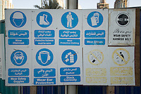 Sign advertising for safety in arabic and english outside a buildingsite. Dubai, one of the seven emirates and the most populous of the United Arab Emirates sits on the southern coast of the Persian gulf.