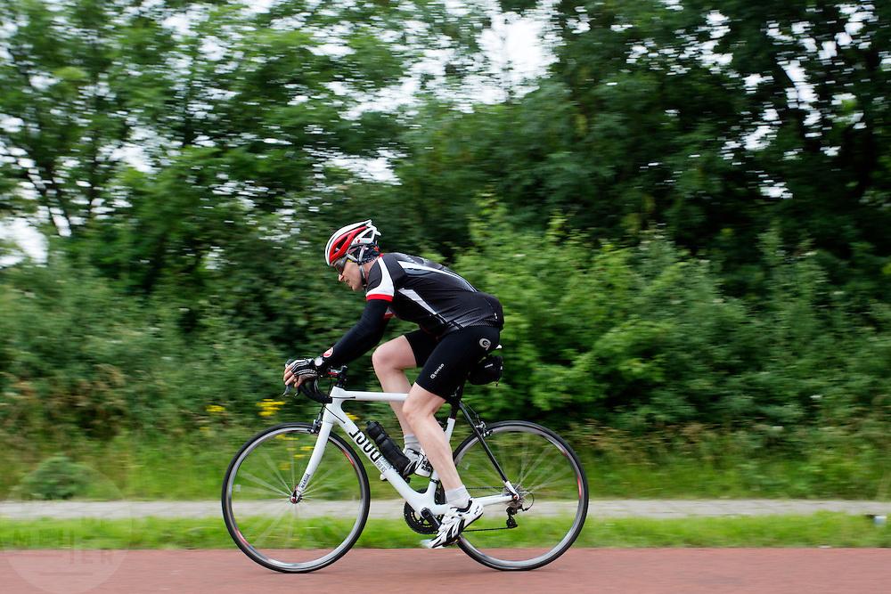 Een racefietser rijdt over het Rijn-Waalpad, de snelfietsroute tussen Arnhem en Nijmegen. Als de route helemaal klaar is, kunnen fietsers binnen 40 minuten van Arnhem naar Nijmegen fietsen. De snelfietsroute kent weinig obstakels en moet het aantrekkelijk maken om ook langere afstanden met de fiets af te leggen.<br /> <br /> A cyclist rides on the Rijn-Waalpad, the fast cycling route between Arnhem and Nijmegen.  When the route is finished, cyclists can get within 40 minutes from Arnhem to Nijmegen. The fast cycle route has few obstacles and to make it attractive to commute long distances by bicycle.