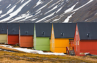 Simply designed row houses contrast with color against a barren mountain background at longyearbyen, Spitsbergan Island, Svalbard, Norway, Scandinavia.