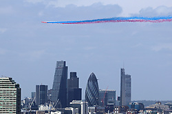 © Licensed to London News Pictures. 10/05/2015.  Today's VE Day anniversary flypast over London as seen from Greenwich. The Red Arrows were seen swooping over London leaving a plume of coloured smoke. Pictured: Red Arrows leave a trail of coloured smoke over the City of London. Credit : Rob Powell/LNP