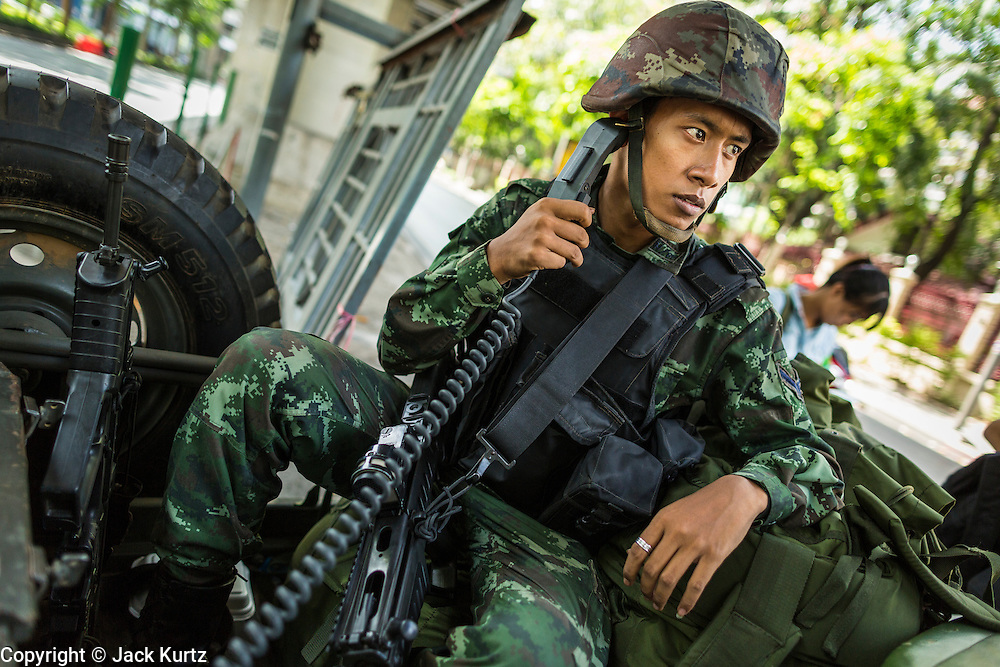 "20 MAY 2104 - BANGKOK, THAILAND:  A Thai soldier with a radio at a checkpoint on Rama I Road in Bangkok. The Thai Army declared martial law throughout Thailand in response to growing political tensions between anti-government protests led by Suthep Thaugsuban and pro-government protests led by the ""Red Shirts"" who support ousted Prime Minister Yingluck Shinawatra. Despite the declaration of martial law, daily life went on in Bangkok in a normal fashion. There were small isolated protests against martial law, which some Thais called a coup, but there was no violence.  PHOTO BY JACK KURTZ"