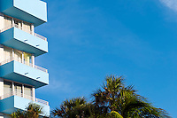 View of art deco balconies and palm trees in Miami Beach.