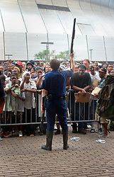 01 Sept, 2005. New Orleans, Louisiana.<br /> Mass evacuation of New Orleans begins. A Louisiana State Trooper holds his shotgun in the air as authorities attempt to hold back thousands of refugees on the verge of chaos awaiting busses out of New Orleans.<br /> Photo©; Charlie Varley/varleypix.com
