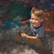 young boy running in dappled shade, on multi-colored concrete tiles,Balboa Park, San Diego
