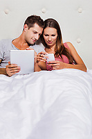 Portrait of young attractive woman showing smartphone while his boyfriend playing games on his digital tablet in bed