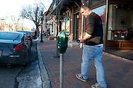 K.T. putting money in a parking meter