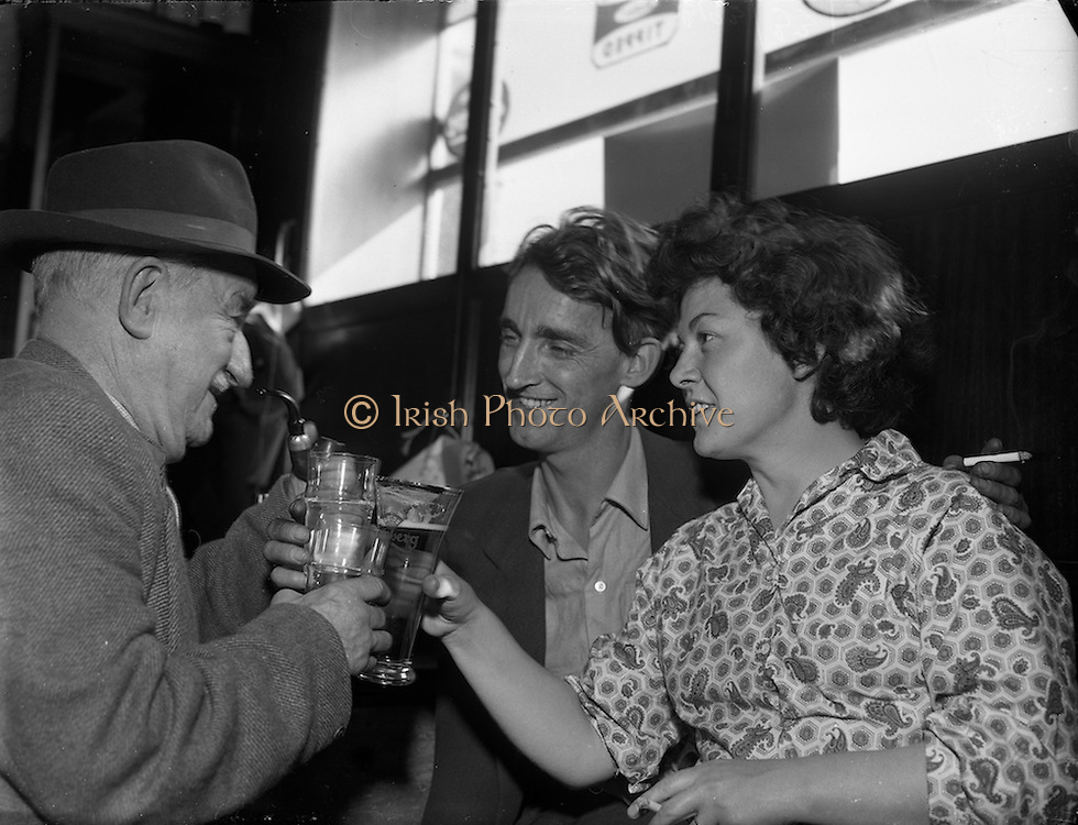"""29/09/1959<br /> 09/29/1959<br /> 29 September 1959<br /> Dominic Behan.<br /> Dominic Behan (centre) with his wife Josephine and his father toast Dublin Critics at Flood's bar, Sundrive Road, Kimmage,  Dublin. Behan's play """"Posterity Be Damned"""" had ben performed at the Gaiety Theatre the night before."""