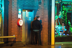 "© Licensed to London News Pictures . 17/12/2016 . Manchester , UK . A man is illuminated by the blue lights of a police van as he is caught urinating in a doorway on Deansgate . Revellers out in Manchester City Centre overnight during "" Mad Friday "" , named for being one of the busiest nights of the year for the emergency services in the UK . Photo credit : Joel Goodman/LNP"