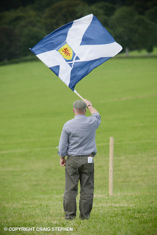 Man standing in field waving a saltire / St Andrews Cross - Scottish flag