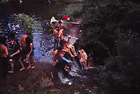 Young people playing in a stream and waterfall,  during the Woodstock music festival in 1969